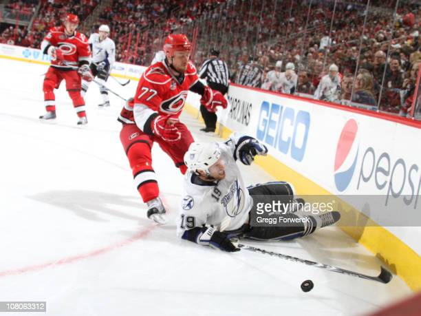 Dominic Moore of the Tampa Bay Lightning goes down in the corner in front of Joe Corvo of the Carolina Hurricanes during a NHL game on January 15...