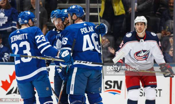 Dominic Moore of the Toronto Maple Leafs celebrates his goal with teammates Roman Polak and Travis Dermott as Lukas Sedlak of the Columbus Blue...