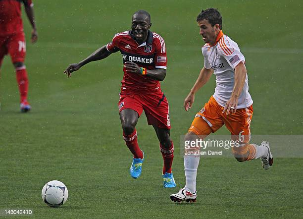 Dominic Oduro of the Chicago Fire and Nathan Sturgis of the Houston Dynamo chase down the ball during an MLS match at Toyota Park on April 15 2012 in...