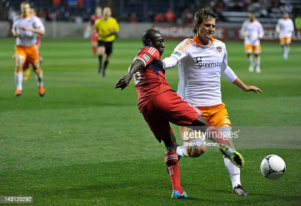Dominic Oduro of the Chicago Fire kicks the ball as Bobby Boswell of the Houston Dynamo defends at Toyota Park on April 15 2012 in Bridgeview...