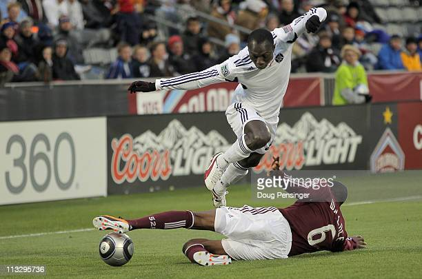 Dominic Oduro of the Chicago Fire leaps to avoid the sliding tackle of Anthony Wallace of the Colorado Rapids at Dick's Sporting Goods Park on April...