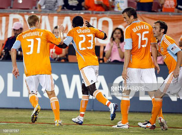 Dominic Oduro of the Houston Dynamo celebrates his score with Andrew Hainult and Cam Weaver against the New England Revolution at Robertson Stadium...