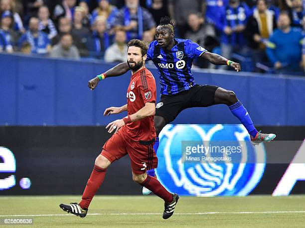 Dominic Oduro of the Montreal Impact jumps behind Drew Moor of the Toronto FC during leg one of the MLS Eastern Conference finals at Olympic Stadium...
