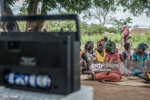 Dominic Ongwen's extended family listen to the sentencing on a radio in Coorom, Ongwen's home village, Uganda, on May 6, 2021. - The International...