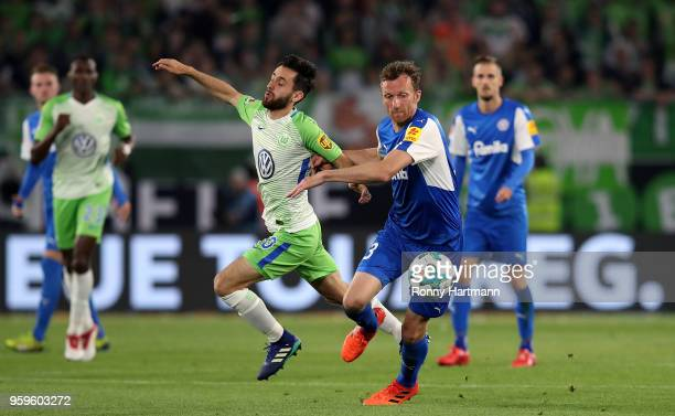 Dominic Peitz of Holstein Kiel and Yunus Malli of Wolfsburg vie during the Bundesliga Playoff Leg 1 match between VfL Wolfsburg and Holstein Kiel at...