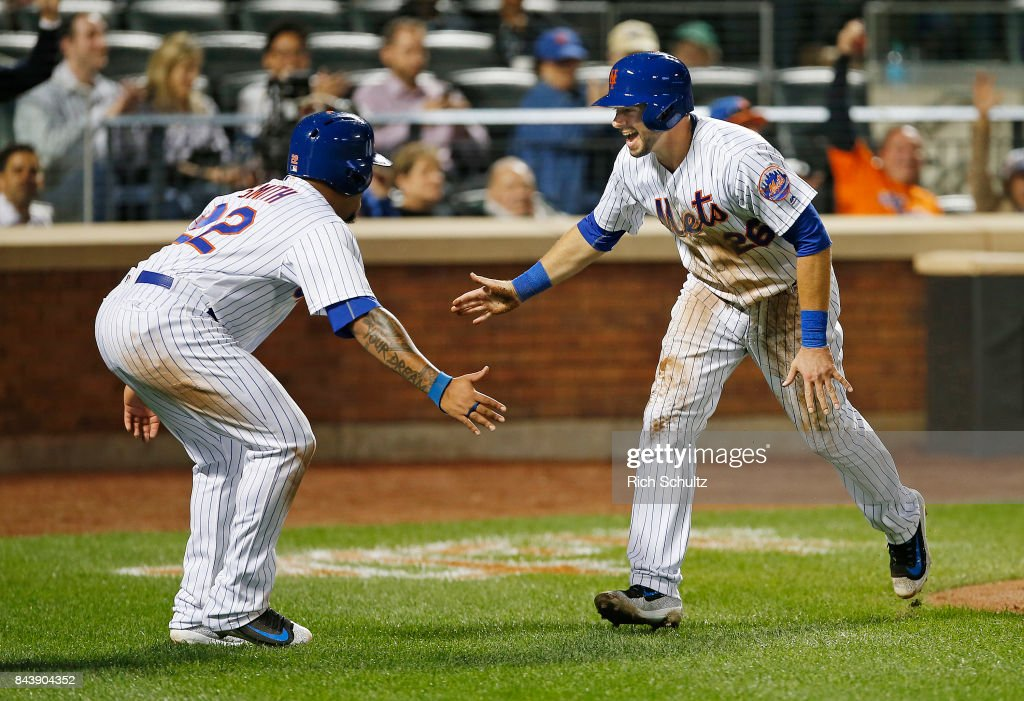 Dominic Smith #22 and Kevin Plawecki #26 of the New York Mets congratulate each other after scoring on a double by Jose Reyes #7 against the Cincinnati Reds during the fourth inning of a game at Citi Field on September 7, 2017 in the Flushing neighborhood of the Queens borough of New York City.