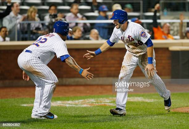 Dominic Smith and Kevin Plawecki of the New York Mets congratulate each other after scoring on a double by Jose Reyes against the Cincinnati Reds...