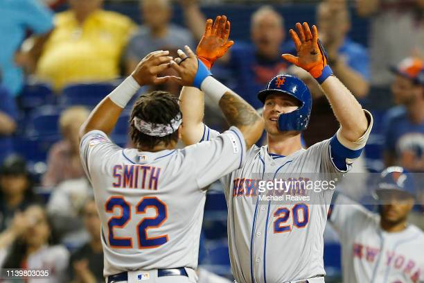 Dominic Smith of the New York Mets celebrates with Pete Alonso after scoring a run in the ninth inning against the Miami Marlins at Marlins Park on...