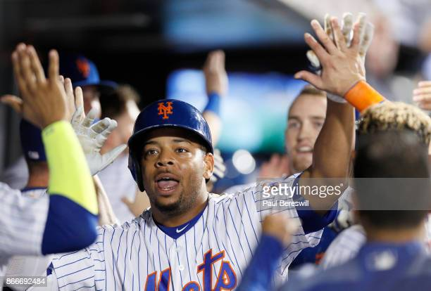 Dominic Smith of the New York Mets celebrates with teammates in the dugout after Smith hit a home run during the Mets last home game of the season in...