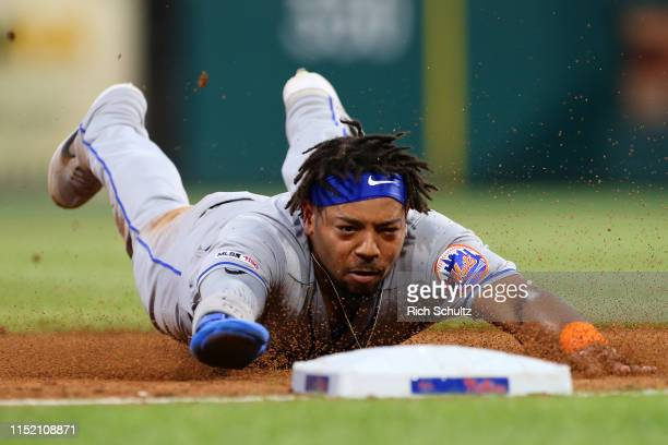Dominic Smith of the New York Mets dives safely into third base after stealing second and advancing on a throwing error by catcher JT Realmuto of the...