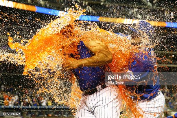 Dominic Smith of the New York Mets has gatorade dumped on him after hitting a walkoff 3run home run in the bottom of the eleventh inning against the...
