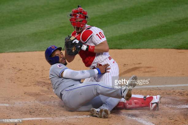 Dominic Smith of the New York Mets is tagged out attempting to score on a single by Kevin Pillar by catcher J.T. Realmuto of the Philadelphia...