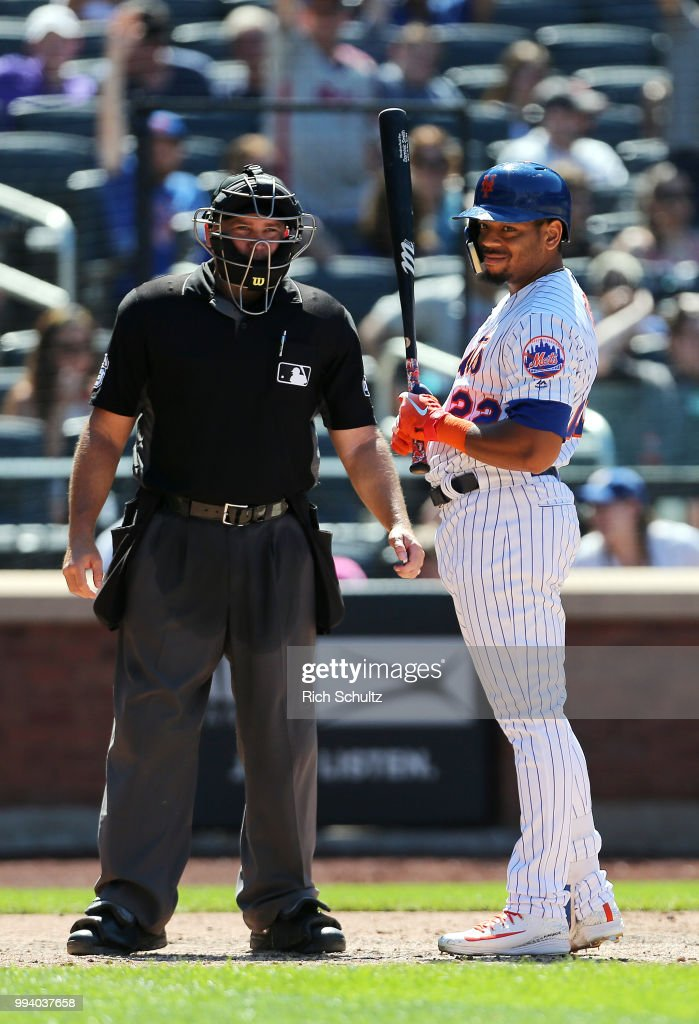 Dominic Smith #22 of the New York Mets reacts to being called out on a third strike by home plate umpire Mark Carlson #6 in the eighth inning, Smith's third of the game against the Tampa Bay Rays at Citi Field on July 8, 2018 in the Flushing neighborhood of the Queens borough of New York City. The Rays defeated the Mets 9-0.