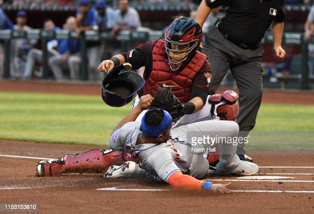 Dominic Smith of the New York Mets scores on a double by teammate Pete Alonso ahead of the tag by Alex Avila of the Arizona Diamondbacks during the...