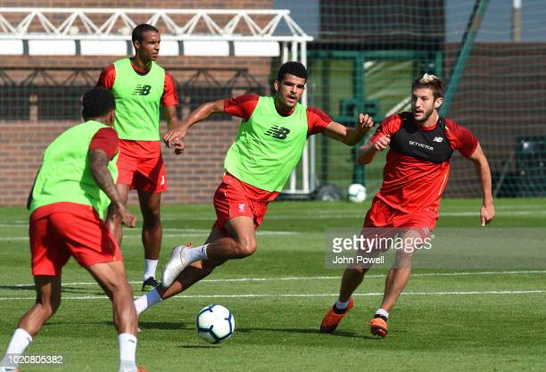 Dominic Solanke and Adam Lallana of Liverpool during a training session at Melwood Training Ground on August 21 2018 in Liverpool England