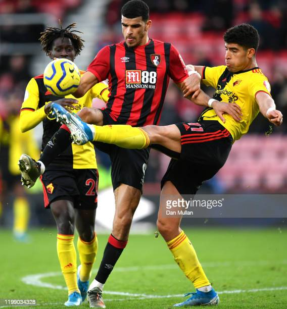 Dominic Solanke of AFC Bournemouth is tackled by Adam Masina and Domingos Quina of Watford during the Premier League match between AFC Bournemouth...