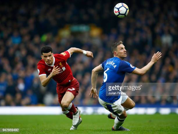 Dominic Solanke of Liverpool and Phil Jagielka of Everton chase the ball during the Premier League match between Everton and Liverpool at Goodison...