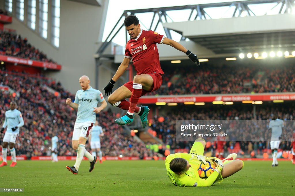 Dominic Solanke of Liverpool jumps over the advancing West Ham goalkeeper Adrian during the Premier League match between Liverpool and West Ham United at Anfield on February 24, 2018 in Liverpool, England.