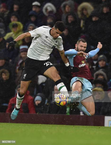 Dominic Solanke of Liverpool with Phil Bardsley during the Premier League match between Burnley and Liverpool at Turf Moor on January 1 2018 in...