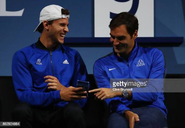 Dominic Thiem and Roger Federer of Team Europe look at Dominic Thiems phone as Alexander Zverev of Team Europe plays his mens singles match against...