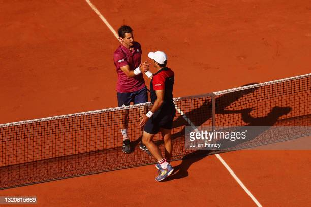 Dominic Thiem of Austria and Pablo Andujar of Spain shake hands at the net after their First Round match during Day One of the 2021 French Open at...