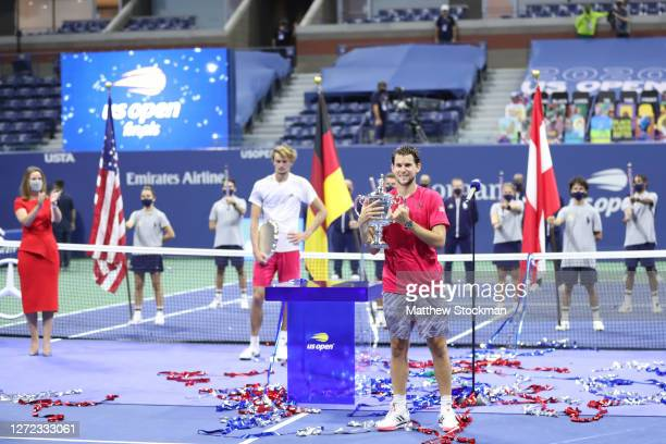 Dominic Thiem of Austria celebrates with his championship trophy as Alexander Zverev of Germany holds his finalist trophy after Thiem won in a...