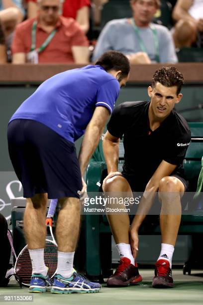 Dominic Thiem of Austria consults with ATP trainer David Pires in the second set to Pablo Cuevas of Uraguay during the BNP Paribas Open at the Indian...