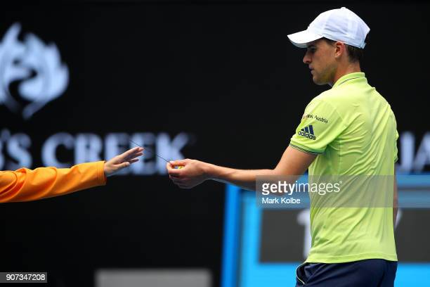 Dominic Thiem of Austria hands a ball kid some debris from the court in his third round match against Adrian Mannarino of France on day six of the...