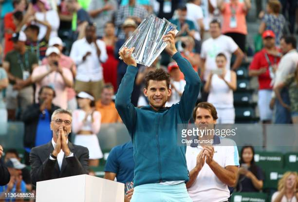 Dominic Thiem of Austria holds the championship trophy aloft after his men's singles final victory against Roger Federer of Switzerland on day...