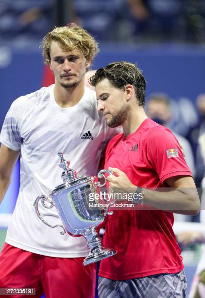 Dominic Thiem of Austria holds with championship trophy as he embraces Alexander Zverev of Germany after their Men's Singles final match on Day...