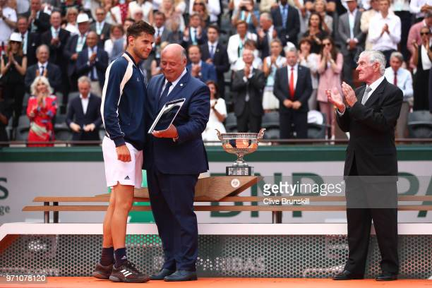 Dominic Thiem of Austria is presented with the runners up trophy following defeat in the mens singles final against Rafael Nadal of Spain during day...