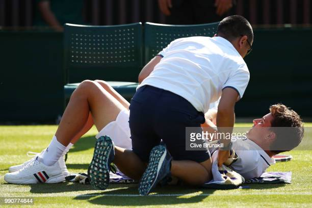 Dominic Thiem of Austria is treated for an injury during his Men's Singles first round match against Marcos Baghdatis of Cyprus on day two of the...