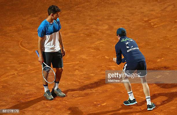 Dominic Thiem of Austria looks on as a ball boy removes a moth from the court during his match against Kei Nishikori of Japan during day six of the...