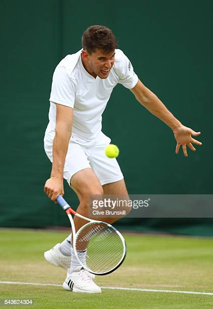 Dominic Thiem of Austria plays a backhand during the Men's Singles first round match against Florian Mayer of Germany on day three of the Wimbledon...