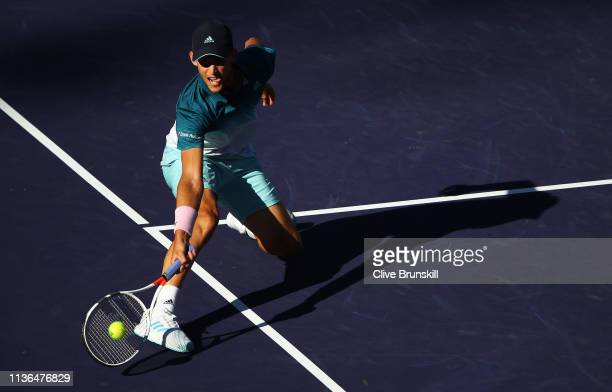 Dominic Thiem of Austria plays a forehand volley against Roger Federer of Switzerland during their men's singles final on day fourteen of the BNP...