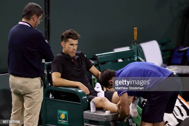 Dominic Thiem of Austria receives treatment from ATP trainer David Pires after losing the second set to Pablo Cuevas of Uraguay during the BNP...