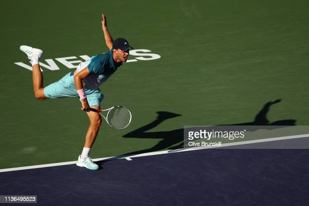 Dominic Thiem of Austria serves against Roger Federer of Switzerland during their men's singles final on day fourteen of the BNP Paribas Open at the...