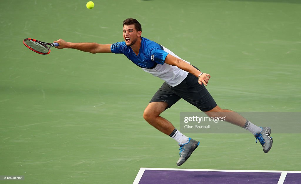 Dominic Thiem of Austria stretches to play a forehand against Novak Djokovic of Serbia in their fourth round match during the Miami Open Presented by Itau at Crandon Park Tennis Center on March 29, 2016 in Key Biscayne, Florida.