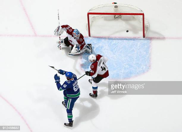 Dominic Toninato of the Colorado Avalanche looks on as Brendan Gaunce of the Vancouver Canucks celebrates after Vancouver goal during their NHL game...
