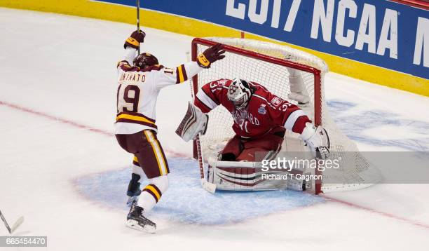 Dominic Toninato of the Minnesota Duluth Bulldogs celebrates a goal by teammate Joey Anderson against Merrick Madsen of the Harvard Crimson during...