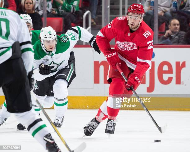 Dominic Turgeon of the Detroit Red Wings skates with the puck up ice followed by Remi Elie of the Dallas Stars during an NHL game at Little Caesars...