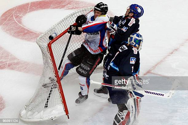 Dominic Walsh of Ingolstadt is challenged by Ronny Arendt and goalkeeper Lukas Lang of Mannheim during the DEL match between Adler Mannheim and ERC...