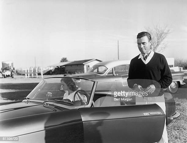 Dominican diplomat and socialite Porfirio Rubirosa dressed ina sweater and scarf holds his keys as he gets into his car where his wife actress Odile...