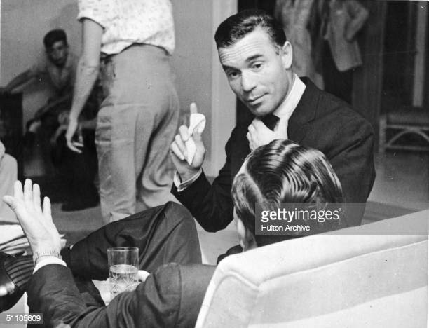 Dominican diplomat and socialite Porfirio Rubirosa gestures with one hand and adjusts his tie with the other while he speaks to an unidentifed man...