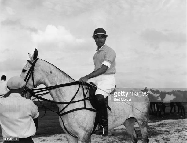 Dominican diplomat and socialite Porfirio Rubirosa on a horse dressed in riding clothes while an unidentifed attendant adjusts the horse's bridle...