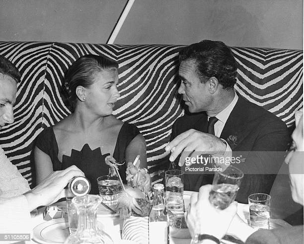 Dominican diplomat and socialite Porfirio Rubirosa smokes cigarettes with Mrs Messmore Kendall at the El Morocoo restaurant New York New York 1950s