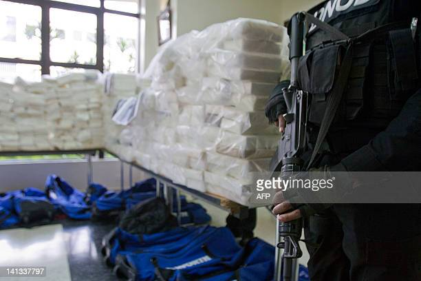 Dominican drug squad policemen stand guard next to packs containing 8074 kilos of cocaine confiscated by Dominican Drugs Control National Direction...