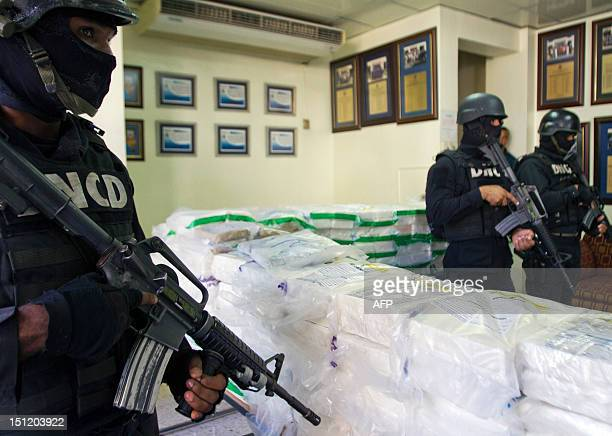 Dominican drug squad policemen stand guard next to packs containing 777 kilos of cocaine confiscated by the Dominican National Direction of Drug...