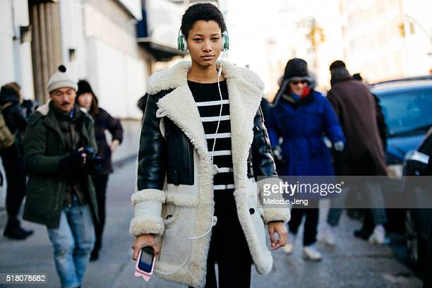 Dominican model Lineisy Montero exits the Lacoste show at Spring Studios in long Coach bomber jacket with shearling and leather and green Beats...