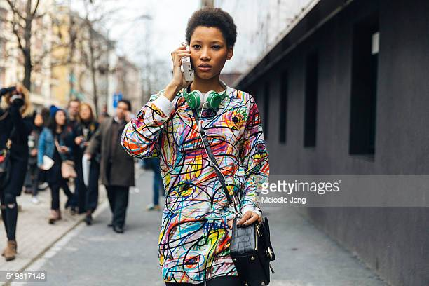 Dominican model Lineisy Montero talks on the phone with her Moschino phone and wears an artthemed white top green Beats headphones and a black purse...